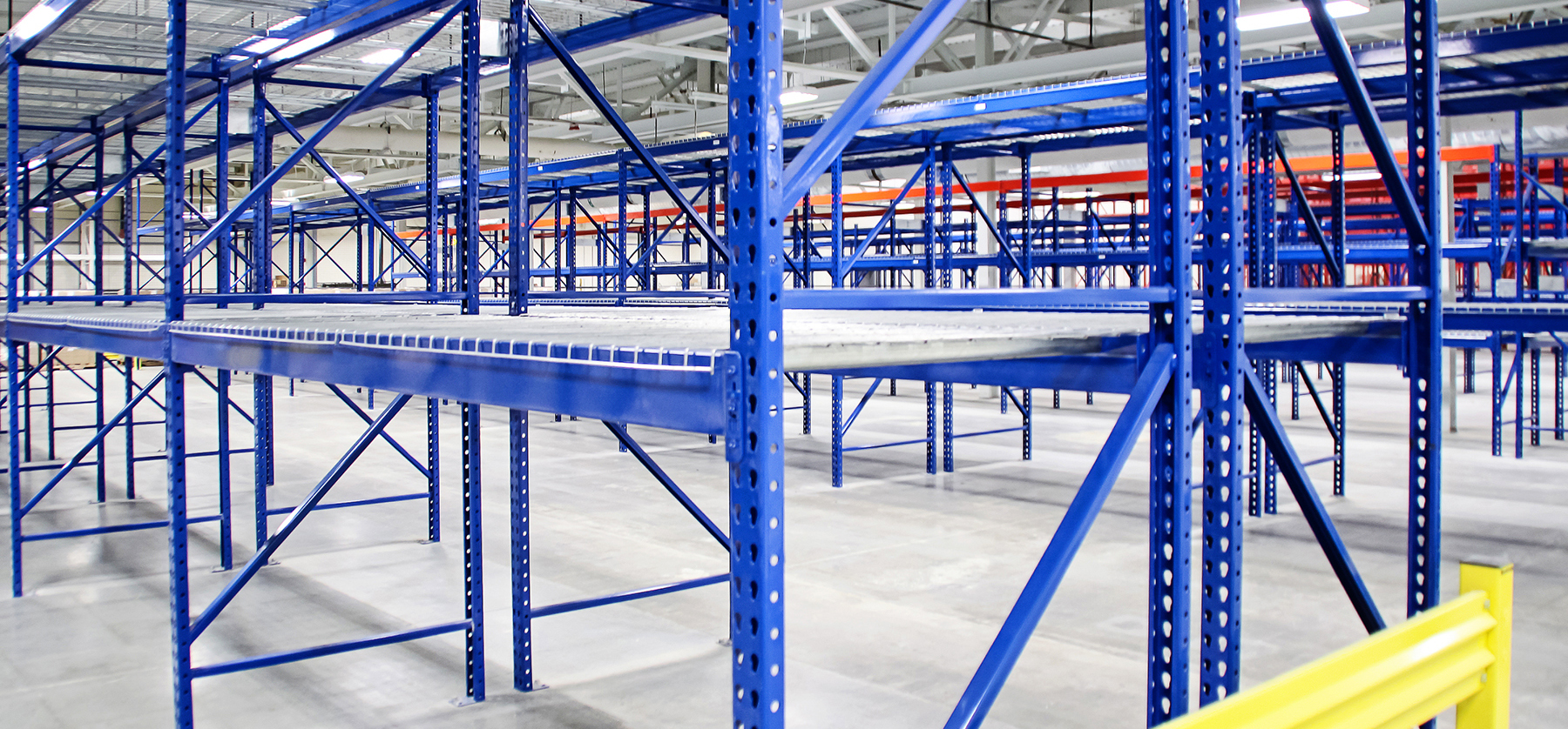 Custom colored galvanized pallet racks with mesh decking in a warehouse